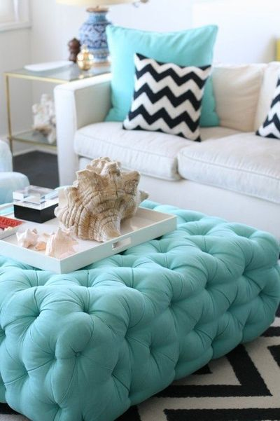 black white and teal living room. tufted teal ottoman  modern white couch with black and chevron throw pillow rug whit