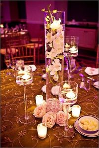Submerged flowers in vases surrounded by candles