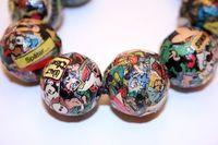 Pne-of-a-kind découpaged jewelry Craftster user Munk Munk created using colorful scraps of comic book pages, Mod Podge, wooden beads and bangles.