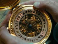 This is the alethiometer, which is a device that can answer any question you ask it provided you can understand its symbols. Mrs. Coulter was trying to steal it from Lyra to use against Lord Asriel.