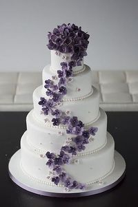 Maybe use the concept, but not this cake exactly. 4 tiers instead of five. Separate the top two from the bottom two. Have the top of this cake (the flowers) in the center in between the two halves. Maybe find a figurine topper. Oh, and not purple,...