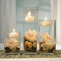 floating candles. flowers. rocks. great centerpiece idea.