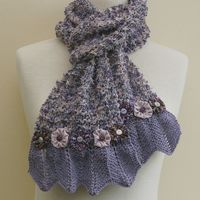 A scarf adorned with pretty, yo-yo flowers in shades of purple and pink.