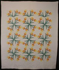 Daffodils Quilt: Circa 1920. Slightly abstracted Daffodils are very effectively conveyed in soft shades of yellow and coral. Close placement of the blocks creates a secondary pattern of circular wreaths of daffodils. Half blocks meant to cover the pillows...