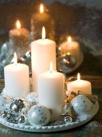 bhg Light a Candle Add some shimmer and shine to your holiday decor with candles and sparkly silver-and-white ornaments. Arrange chunky pillar candles (in varying heights) on a round tray and surround with Christmas ornaments, rhinestone jewelry, ...