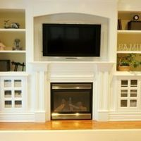 Family room idea to combine the Flat Screen TV & a Fireplace with cabinetry on either side built-in by Jennifer Brouwer